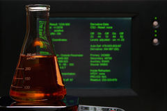 Laboratory Experiment in Science Research Lab. Laboratory glass conical Erlenmeyer flask filled with orange liquid in front of a computer monitor screen with Royalty Free Stock Photography