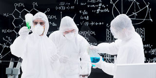 Laboratory experimental testing. Close-up of three people conducting a laboratory experiment using laboratory transparent tools and a blackboard with formulas Stock Photo