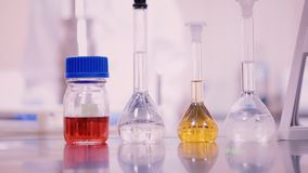 Laboratory flasks and beakers with liquids of different colors on lab table.  stock footage