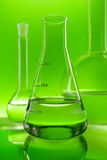 Laboratory flasks on green background Stock Photography