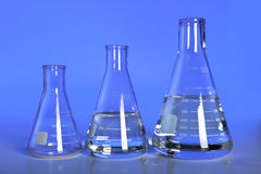 Laboratory Flasks Over Blue Background Stock Photo