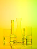 Laboratory glass recipients on yellow background Stock Images