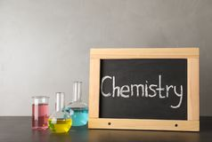 Laboratory glassware and chalkboard with word CHEMISTRY on table against grey background. Space for text stock image