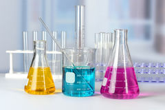 Laboratory Glassware with Colored Solutions. Laboratory glassware with solutions of different colors on table Royalty Free Stock Images