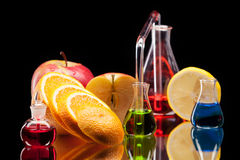 Laboratory glassware with fruits. Still life of laboratory glassware with colorful liquids and fruits on black background Stock Image