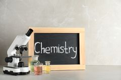 Laboratory glassware, microscope and board with word CHEMISTRY on table against grey background. Space for text royalty free stock images