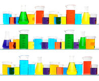 Laboratory Glassware on three Shelves. Assorted sizes and shapes of laboratory glassware on three shelves. Beakers are filled with liquids of assorted colors Stock Images