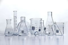 Laboratory Glassware on White Table. Laboratory glassware on white reflective table royalty free stock image