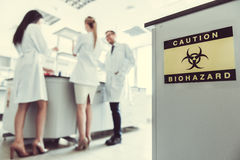 At the laboratory. Inscription `Caution Biohazard`. Medical doctors are working in the background Royalty Free Stock Photography