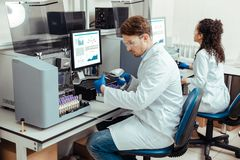 Intelligent young man wearing a lab coat. In the laboratory. Intelligent young men wearing a lab coat while scanning a blood sample royalty free stock photos