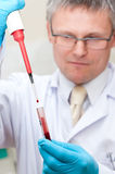 Laboratory man blood testing. Laboratory man holding a special pipette with blood droplet and test tube Royalty Free Stock Images