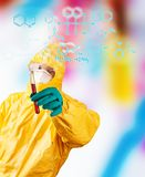 Laboratory man holding vial of blood sample. Laboratory man in chemical protective dress holding vial of blood sample. Chemical formula on foreground Stock Photography