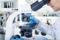 Laboratory Microscope. Scientific and healthcare research background. Photo of a professional microscope close-up with chemist scientific researcher hands using Royalty Free Stock Photos