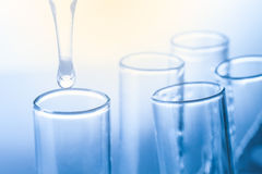 Laboratory pipette with drop of liquid over glass test tube Stock Images