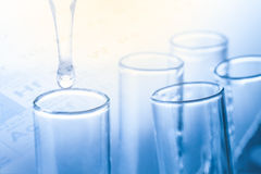 Laboratory pipette with drop of liquid over glass test tubes Royalty Free Stock Images