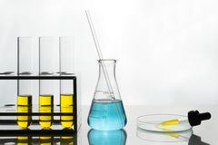 Yellow liquid in test tubes and dropper, blue liquid in flask. Laboratory scene, yellow liquid in test tubes and dropper, blue liquid in flask royalty free stock images