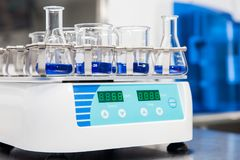 Shaker loaded with erlenmeyers and beakers. Laboratory shaker loaded with erlenmeyers and beakers Royalty Free Stock Photos