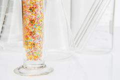 Laboratory sprinkle sugar in glassware for liquids on white back Royalty Free Stock Image