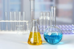 Laboratory Table with Glassware. Laboratory table with colored liquids in flasks stock photos