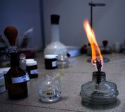 Laboratory table on which there are vials and a container with a burning wick. Photo Stock Image