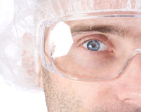 Laboratory technician. A close up view of the right cheek and eye of a male laboratory technician wearing safety glasses and a thin head covering Stock Photos