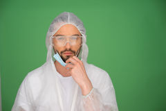 Laboratory technician. Bearded young male laboratory technician in a sterility suit, goggles and a mask on a green background with copyspace Stock Photo