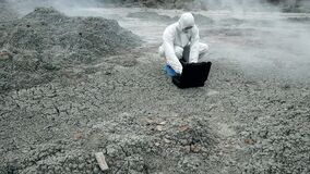 A laboratory technician in a mask and a chemical protective suit opens a toolbox on dry land, around toxic smoke