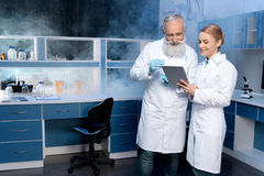 Laboratory technicians in lab coats looking at digital tablet during work in laboratory. Smiling laboratory technicians in lab coats looking at digital tablet royalty free stock photography