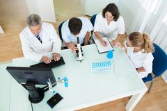 Laboratory technicians at work. Overhead view of four laboratory technicians at work seated around a table reading and recording tests on a microscope and Royalty Free Stock Photo