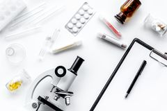 Laboratory test. Microscope, pills, test tube on white background top view Stock Photography