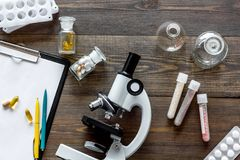 Laboratory test. Microscope, pills, test tube on wooden background top view Stock Images