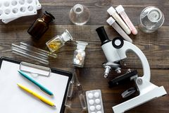 Laboratory test. Microscope, pills, test tube on wooden background top view Stock Photography