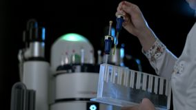 Laboratory woman pulls out the tube with bacteria and viruses. Scientist puts out a glass flask from cooling box. Hands. Holding tubes 4K stock footage