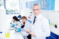 Laboratory work of three. Close up portrait of professor in form. Al wear and special labcoat in glasses holding tablet and looking serious and concentrated stock image