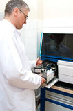 Laboratory worker. Opening cartridge section of blood test machine Royalty Free Stock Photo
