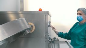 Laboratory worker adjust pharmaceutical machine for mixing powder and granules