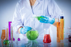 Laboratory worker mixes chemical liquid sample. Royalty Free Stock Photography