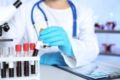 Laboratory worker taking test tube with blood sample. From rack for analysis on table royalty free stock photo