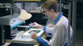 Laboratory worker is using a machine to assemble boards. 4K stock video