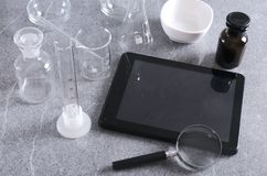 Laboratory workplace, empty glassware for tests, tablet and magnifier on the grey table. Vertical shot. Medical glassware, tablet and magnifier on the stock image