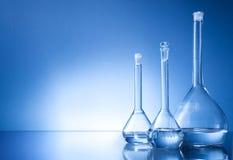 Laborausstattung, Flasche mit drei Gläsern auf blauem Hintergrund Stockbild