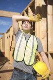 Laborer exhausted on site. Exhausted male laborer wearing reflective vest with hardhat at construction site Stock Photography