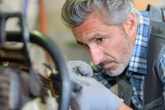 Laborer fixing an equipment. Engine stock photography