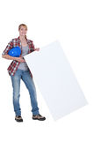 Laborer holding white board Stock Images