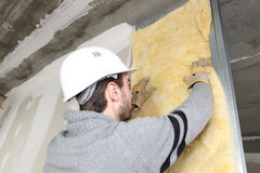 Laborer laying glass wool Royalty Free Stock Image