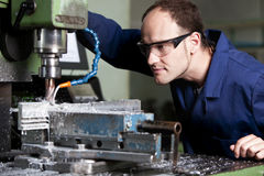 Laborer at milling machine. Blue-collar worker with safety glasses at milling machine in workshop Royalty Free Stock Images