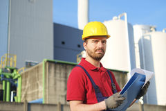 Laborer outside a factory working dressed with safety overalls e. Quipment Royalty Free Stock Photography