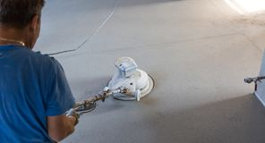 Laborer polishing sand and cement screed floor. Laborer performing and polishing sand and cement screed floor. Sand and cement floor screed stock photography
