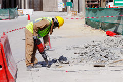 A laborer uses a jackhammer to break up a concrete pavement. A laborer is well protected in safety gear as he uses a jackhammer to break up a reinforced concrete Stock Photos