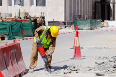 A laborer uses a jackhammer to break up a concrete pavement. A laborer is well protected in safety gear as he uses a jackhammer to break up a reinforced concrete Royalty Free Stock Photos